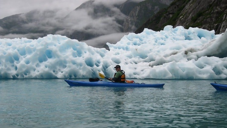 Kayaker beside glacier near Sikumi small ship in Alaska