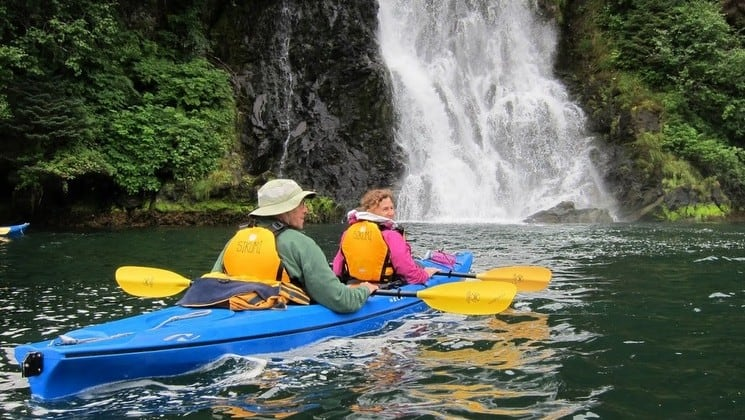 Kayakers paddle by a waterfall near Sikumi yacht in Alaska
