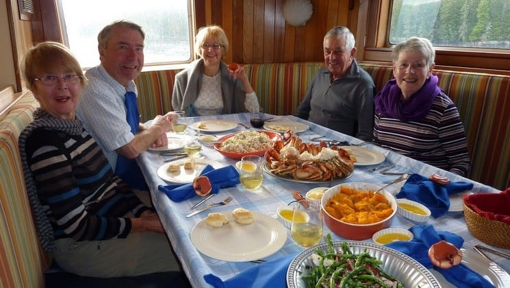 Guests seated around windowside table with family style meal aboard Sikumi yacht in Alaska