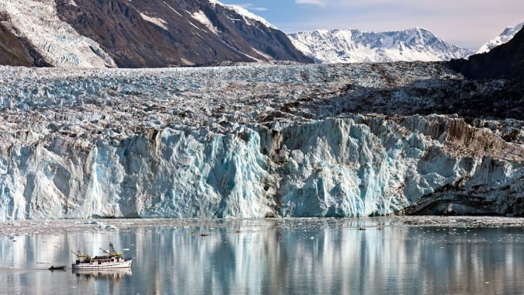 Distant view of starboard side of Discovery yacht dwarfed by huge glacier in Alaska