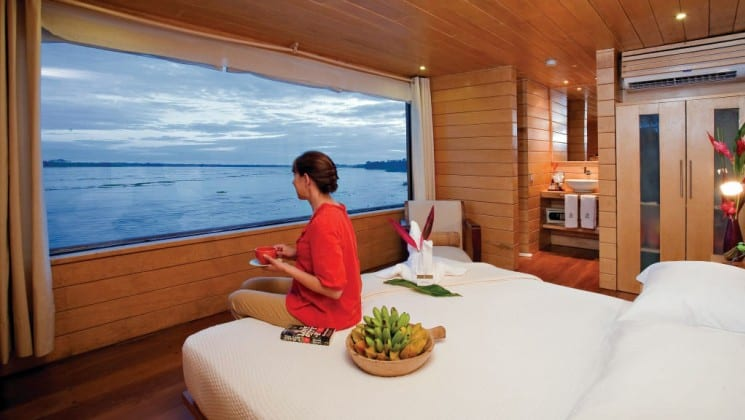 Woman sits on large bed with fruit basket and coffee, looking out large picture window in Suite aboard Delfin II riverboat on Amazon River cruise