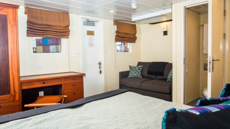 room with a large bed, table, couch and doorway in the Safari Voyager Panama small ship