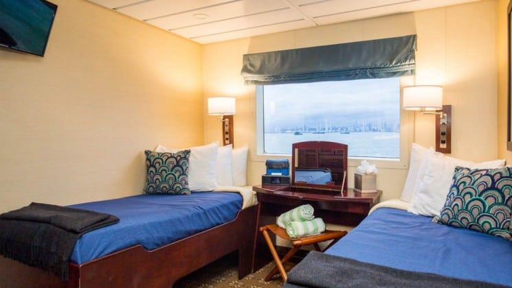 commander cabin with two beds, a table and large window aboard the Safari Voyager Costa Rica small ship