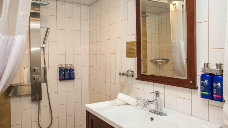 Safari Voyager Panama small ship jr commodore suite bathroom with tile walls, a vanity, sink and mirror