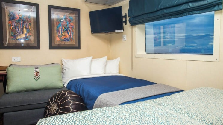 Safari Voyager Costa Rica small ship commodore suite with large bed, tv and picture on the wall and large window
