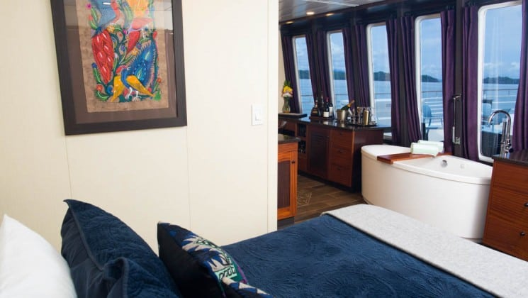 Safari Voyager Panama small ship owner's suite with a large bed, opening to an adjoining room and large windows