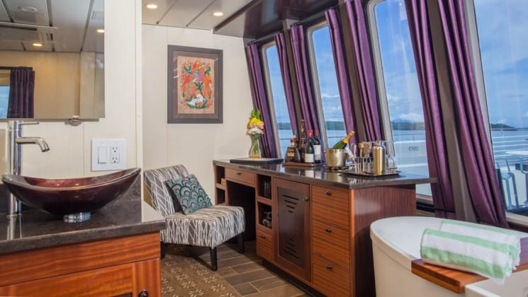 Safari Voyager Costa Rica small ship owner's suite with bathtub, bar, comfortable chair and large windows