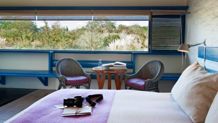 Bed with table and two chairs beneath window with forest views in Yali Room at Explora Atacama Lodge in Chile