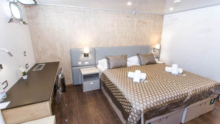 Adriatic Sun cabin room with large bed and desk.