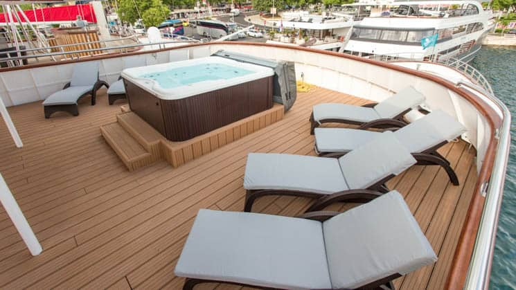 Adriatic Sun hot tub deck with hot tub and chaise lounges.