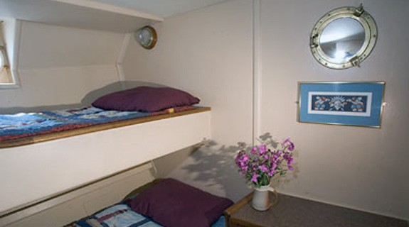 Discovery stateroom with upper and lower single berth and drawers and porthole.