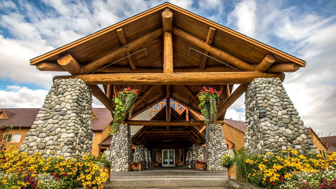 Exterior view of the front door with large stone pillars and A frame at Talkeetna Lodge in Alaska.