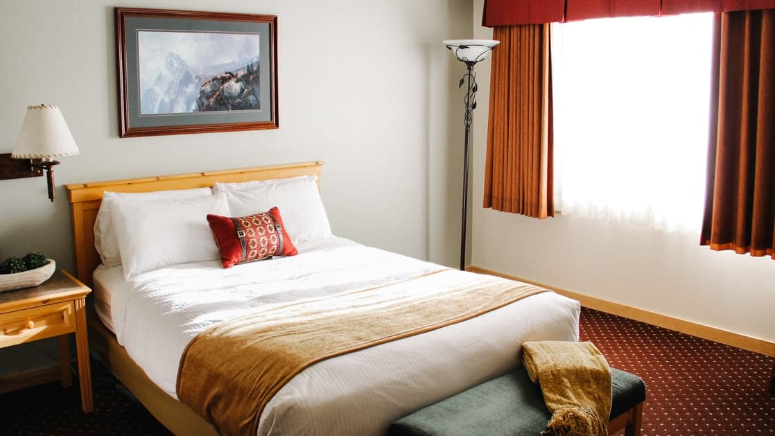 Single large bed made with white sheets and one red accent pillow in the middle next to a window at the Talkeetna Lodge in Alaska.