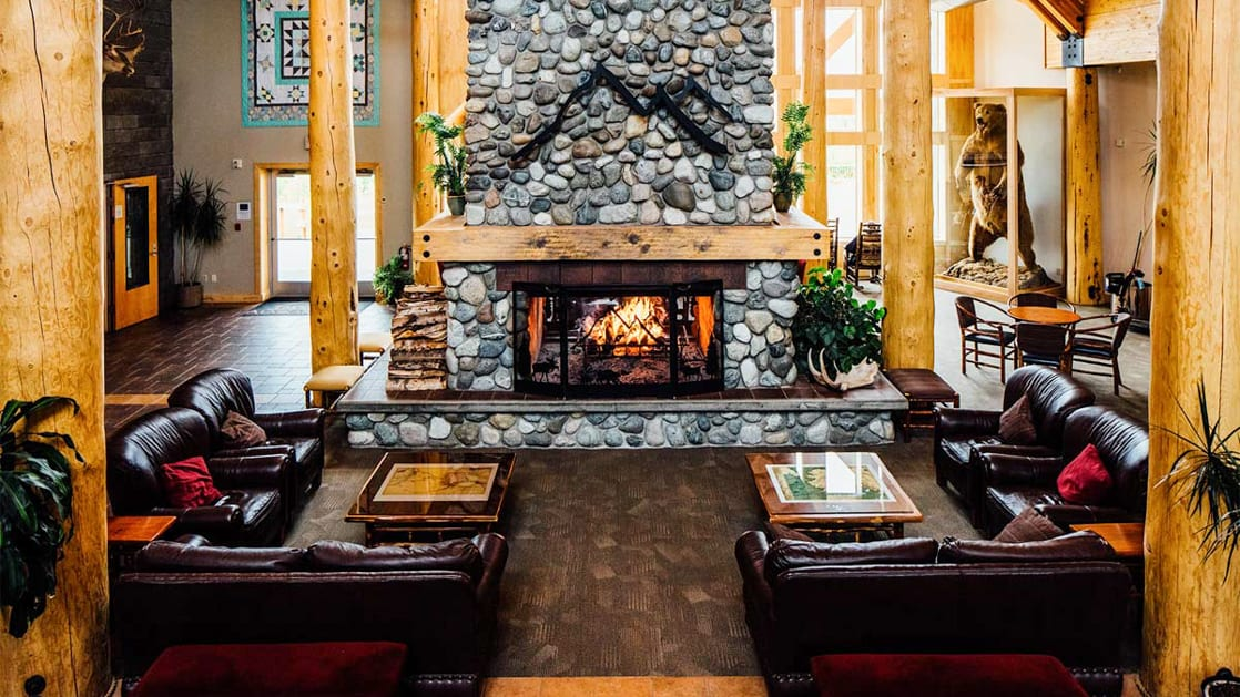 Spacious lobby with river rock fire place with several leather couches surrounding it at Talkeetna Lodge in Alaska.