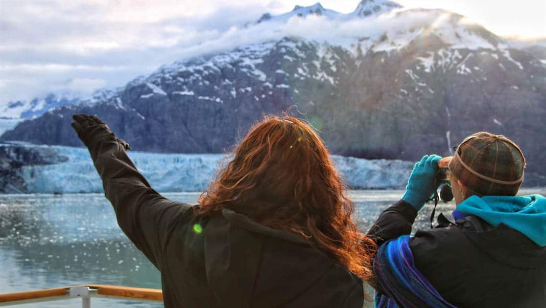 Two guests on deck of their small ship cruise in Alaska looking at the glacier they are approaching