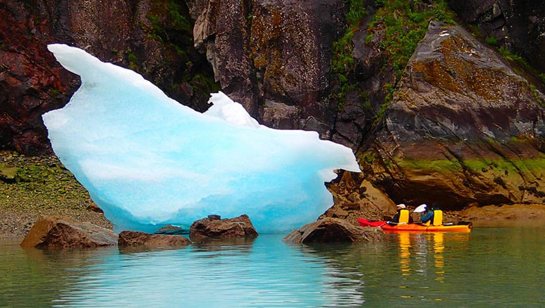 Tandem kayak couple up close to a blue iceberg floating close to rocks on the shore in Alaska.