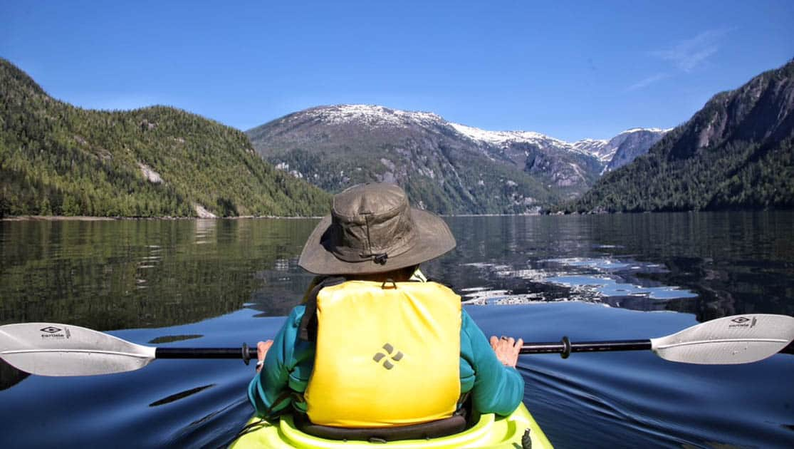Person Kayaking in a calm channel from their small ship Alaska cruise