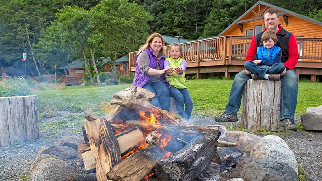 Family sitting around a campfire at Orca Point lodge in Juneau Alaska