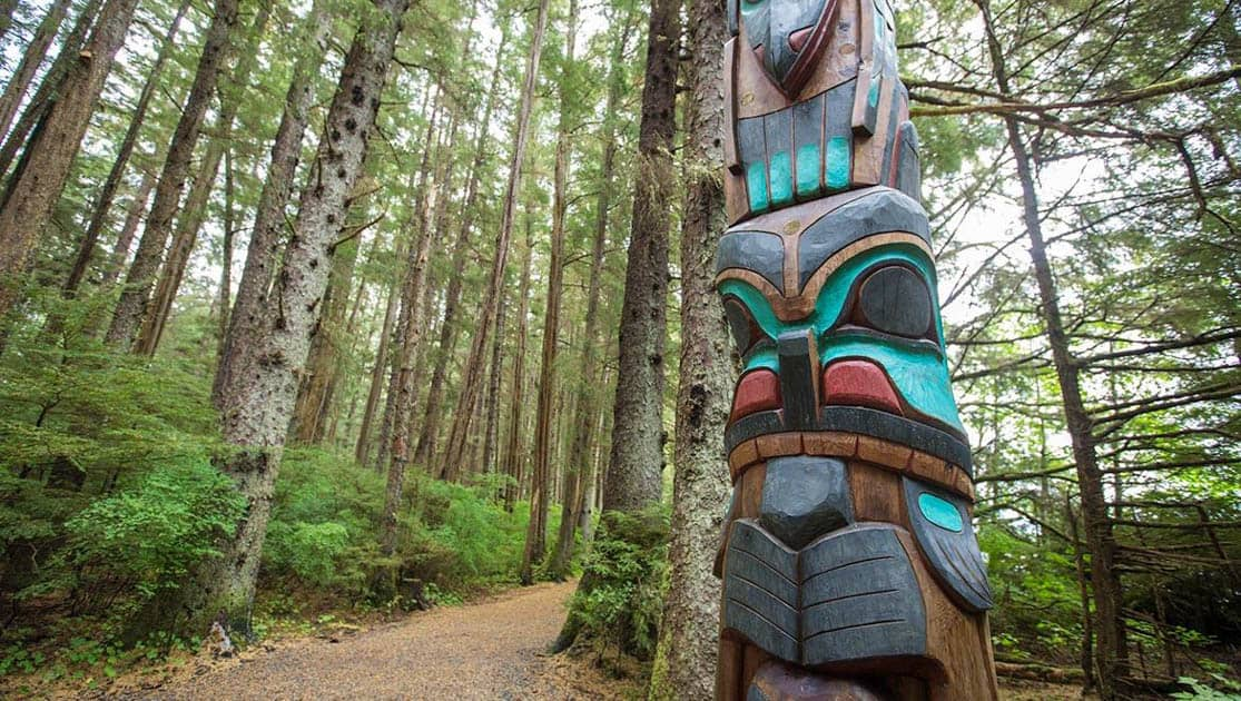 Totem pole seen on a rainforest hike path in south east alaska.