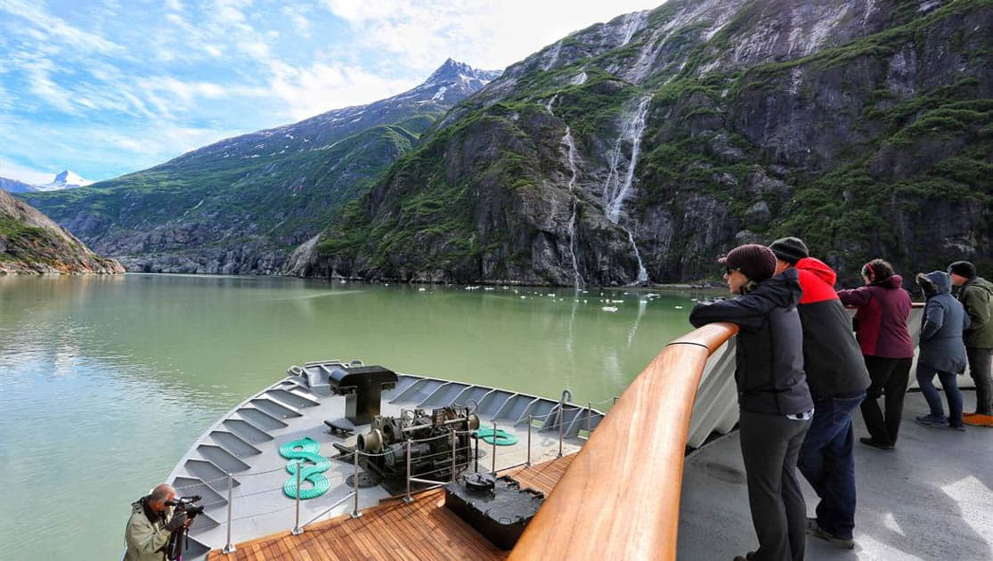 Passengers on a small ship enjoying the view from a deck above the bow as they are cruising past waterfalls coming down the fjords in Alaska.