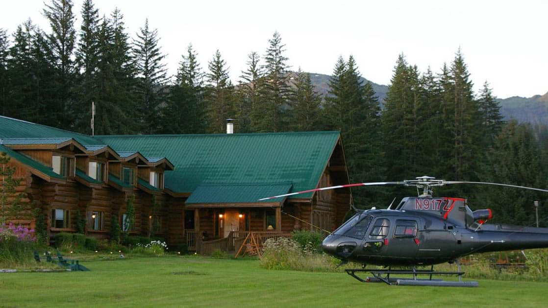 A helicopter is parked on the lawn in front of the Bear Track Inn, a remote lodge ideal for accessing Glacier Bay, Alaska