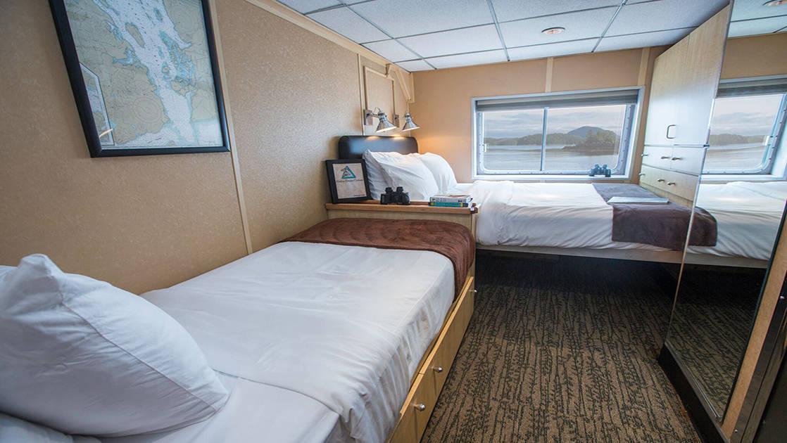 Category A stateroom aboard Baranof Dream with two single beds, window, and mirror.