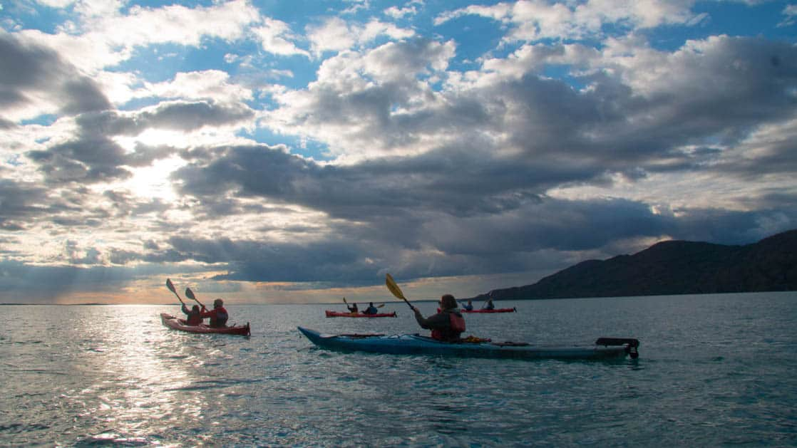 adventure travelers kayaking in the evening on the alaska glacier country small ship cruise