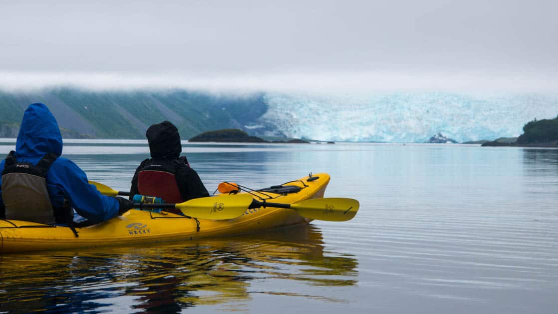 adventure travelers in kayaks looking at an iceberg on the alaska's glacier country small ship cruise