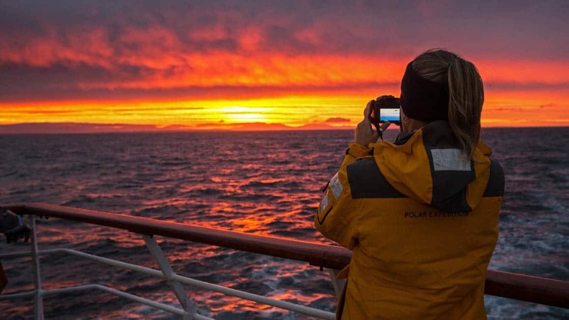 Bright red and yellow sunset from Antarctica Air Cruise with a passenger taking a photo of it from the ship deck