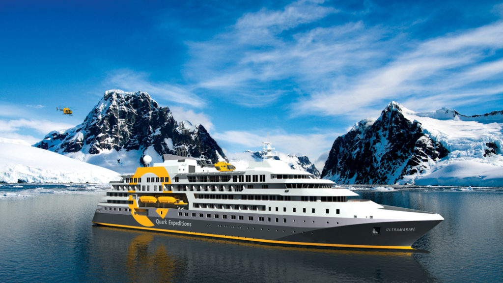 Exterior of Ultramarine polar expedition ship, starboard side, with snowy peaks in the background on a sunny day.