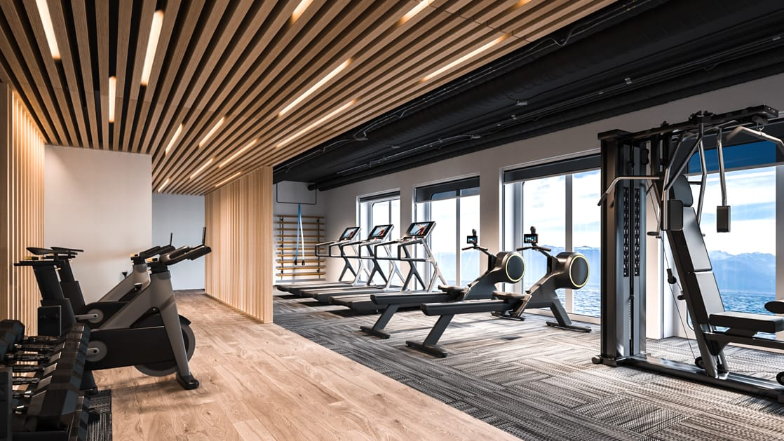 Fitness center with elliptical machines, treadmills, spin bikes and more, looking out onto icy polar waters, aboard Ultramarine expedition ship.