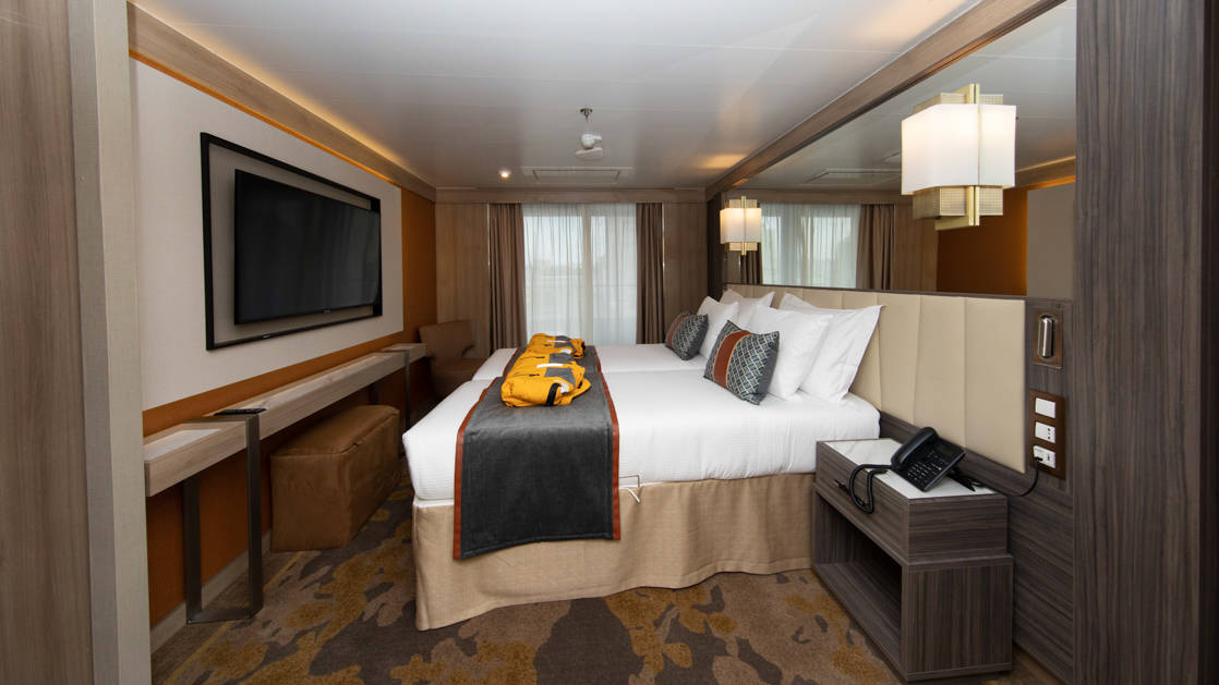 Deluxe Suite aboard World Explorer with double bed, 2 parkas, TV and balcony.