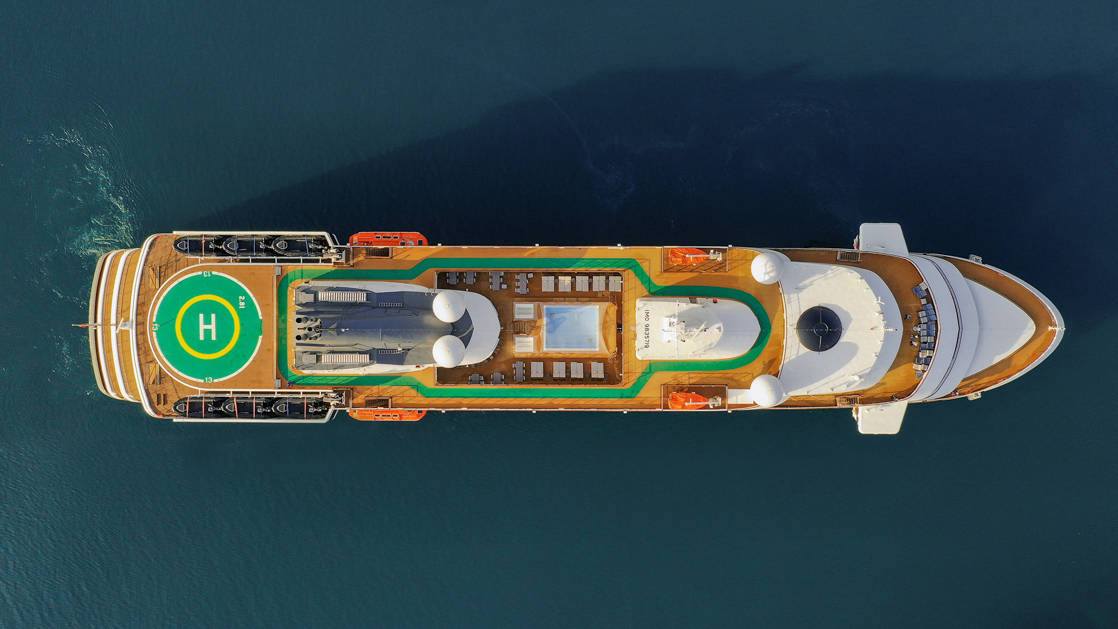 Aerial drone photo of top deck of World Explorer polar small ship with helicopter pad, pool & running track.