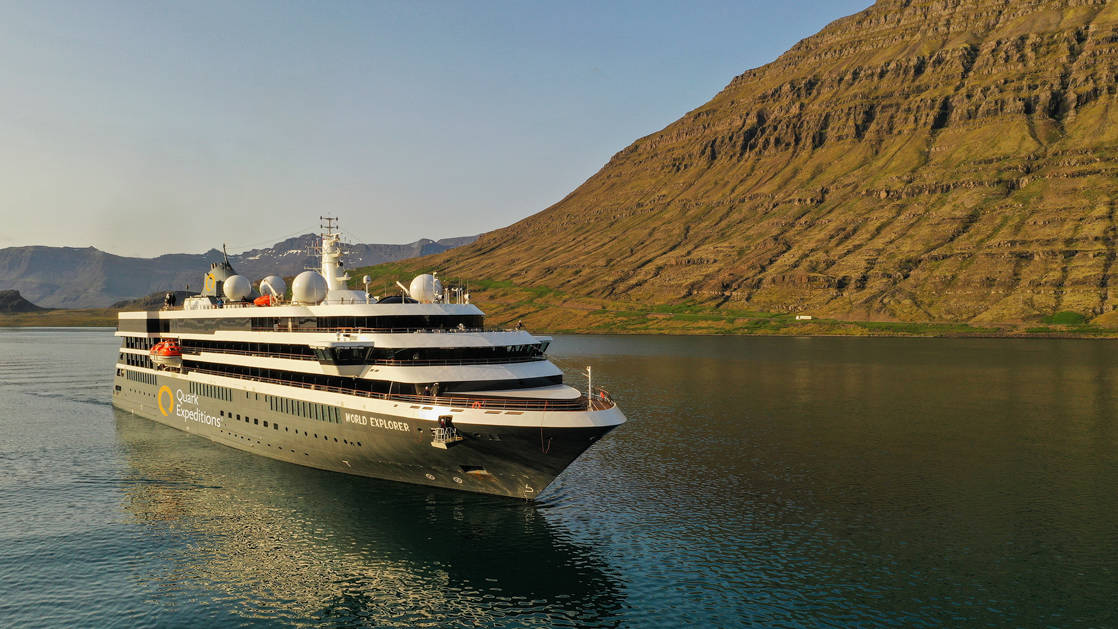 Exterior scenic of polar small ship World Explorer cruising past green and brown hillsides.
