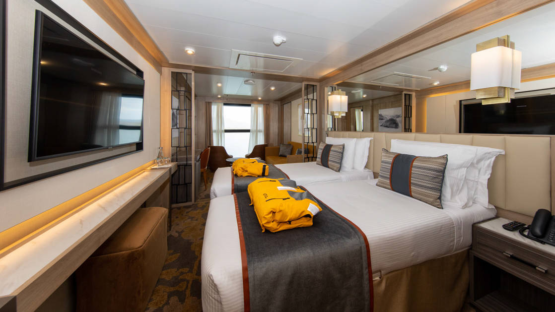 Infinity Suite with 2 beds, 2 parks, TV and seating area aboard World Explorer polar small ship.