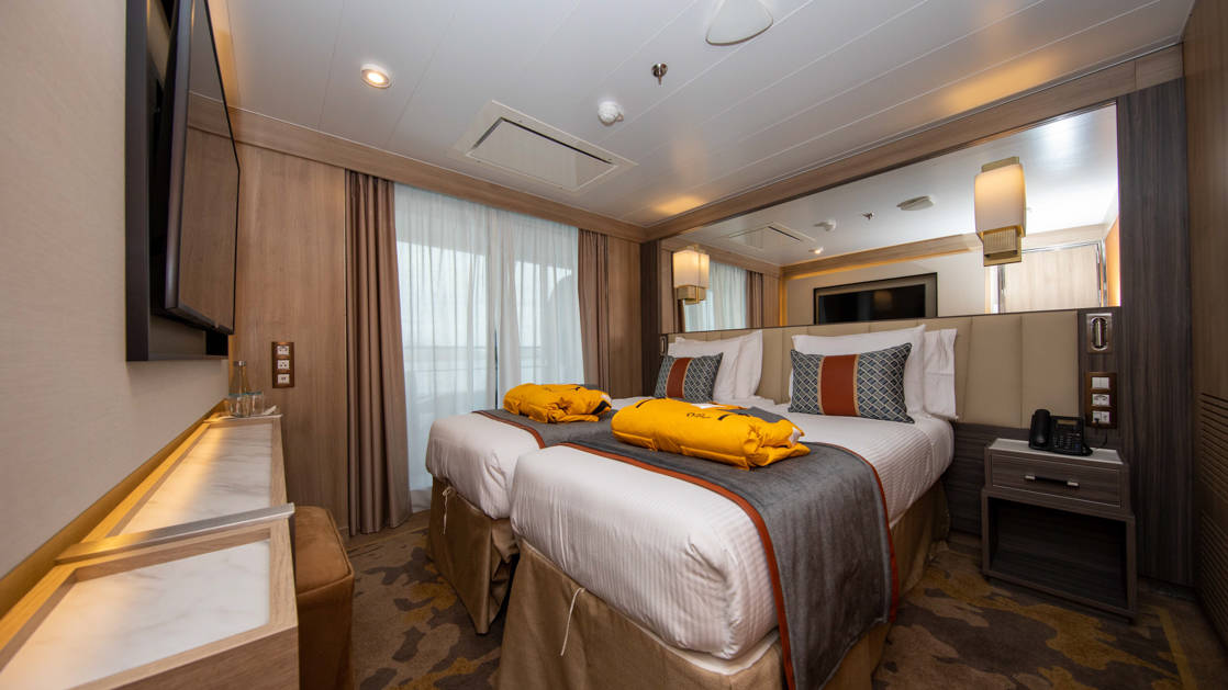 Owner's Suite aboard World Explorer with double bed, sitting area, 2 parkas, TV and balcony.