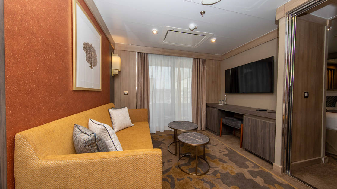 Seating area of Superior Suite with golden-colored couch, coffee tables, wet bar, TV and balcony aboard polar small ship World Explorer.