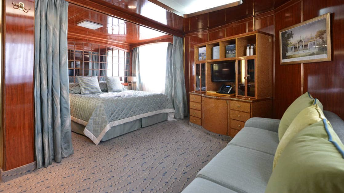 Hebridean Sky Deluxe suite with large picture windows, queen bed, couch and chair, nightstands and dresser.