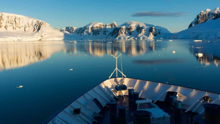 Hebridean Sky bow sailing in Antarctica with snow encased mountains to the front of the boat.