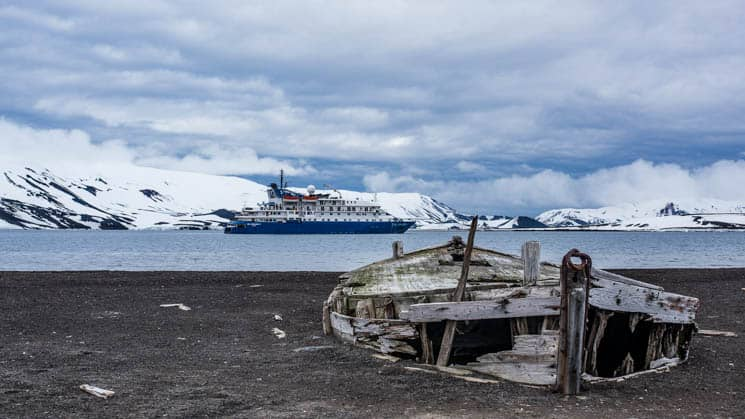 Hebridean Sky anchored off the coast of Antarctica with a old washed up boat on the shore.