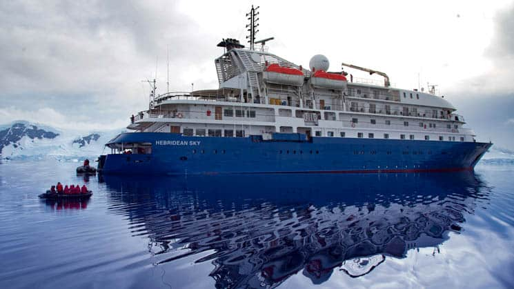 Hebridean Sky Exterior anchored in Antarctica with mountain encased with glaciers and snow.