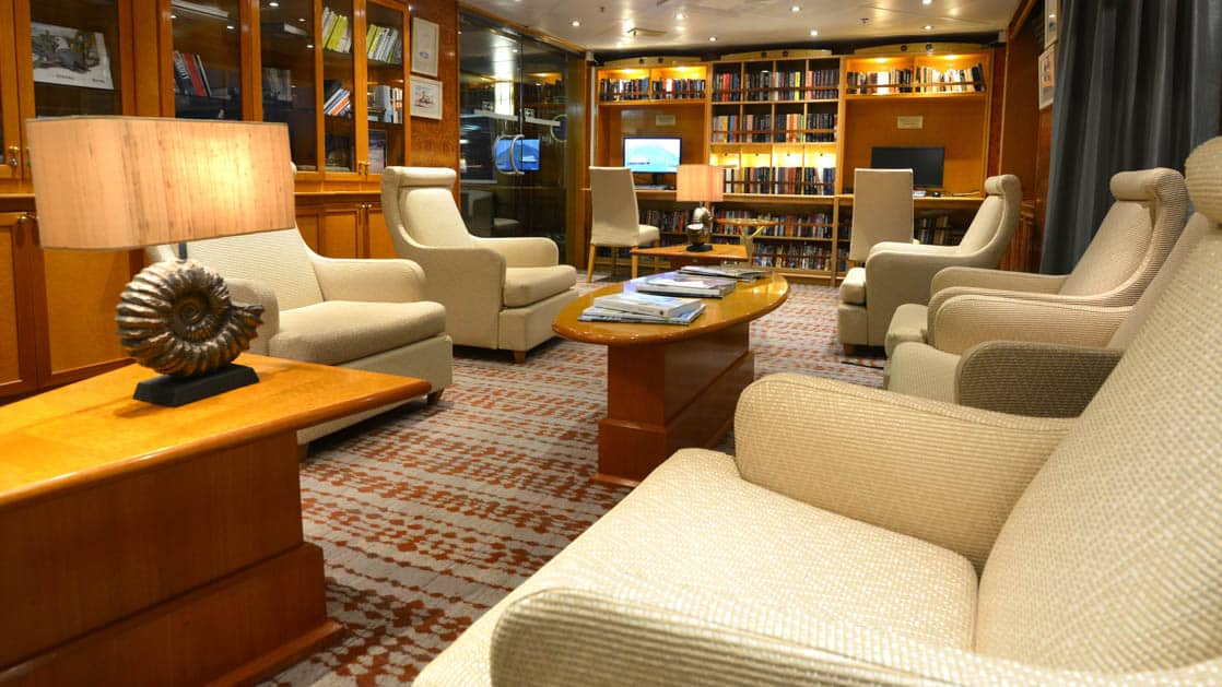 Library and sitting room with books, chairs and tables on board the Hebridean Sky