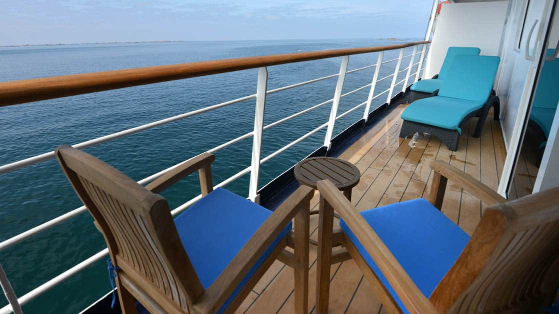 Hebridean Sky Owner's suite balcony with 2 chairs, small table and lounge chair.