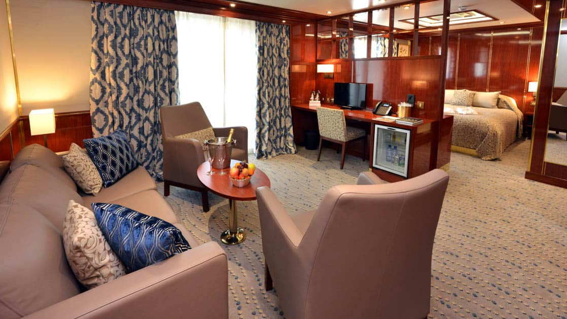 Hebridean Sky Owner's suite with separate queen bedroom and living area with couch, chair, coffee table and desk.