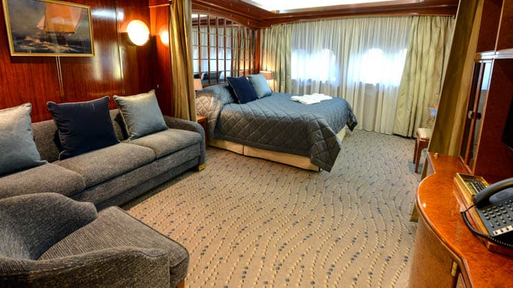 Single Suite aboard Hebridean Sky 21 polar expedition ship, with two twin beds pushed together into a double, two portholes, couch & chair, all in dark blue linens with light tan accents.
