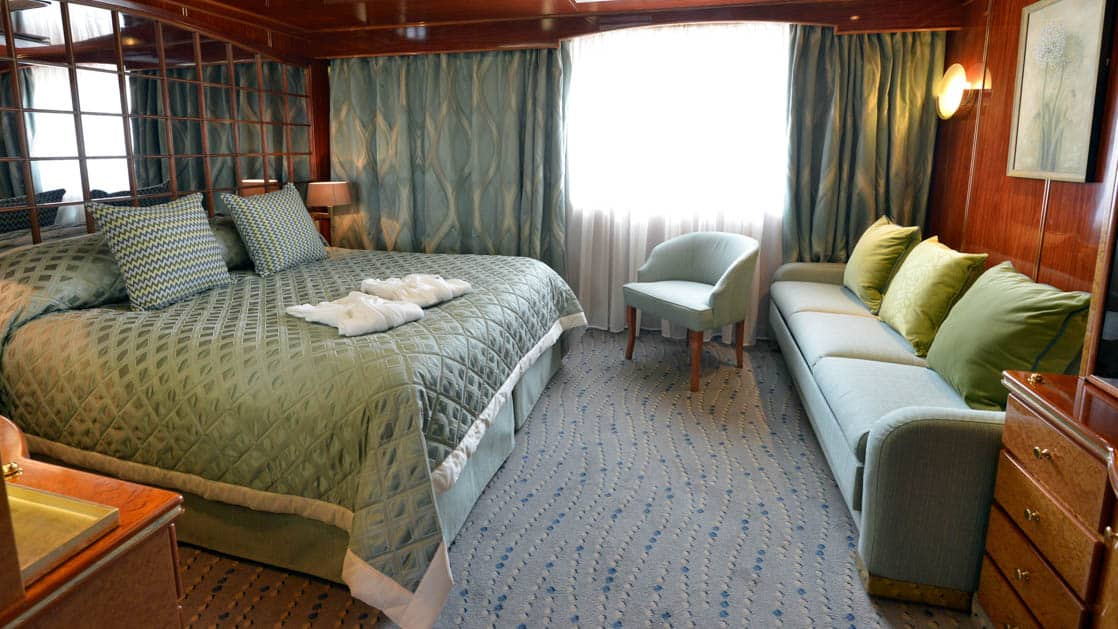 Hebridean Sky Promenade suite with large picture window, queen bed, couch, chair and desk.