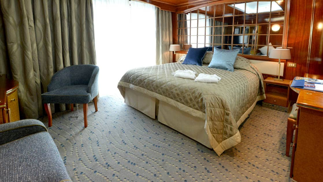 Hebridean Sky Veranda suite with sliding glass door out to the balcony, queen bed, couch and chair, nightstands and desk.