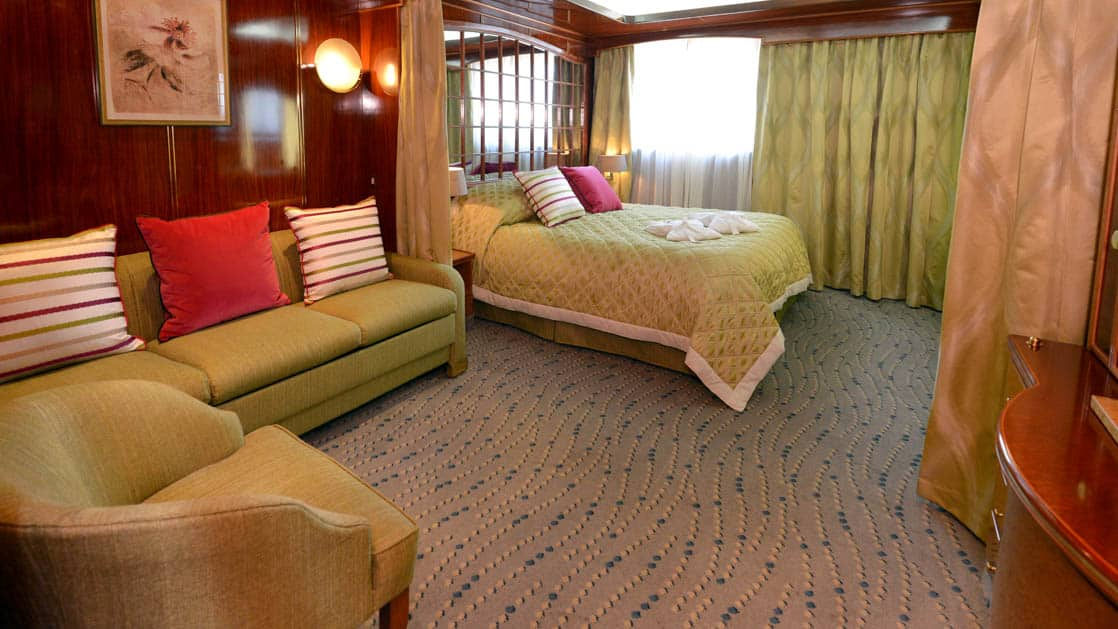Hebridean Sky Window suite with queen bed, couch and living room with large window.