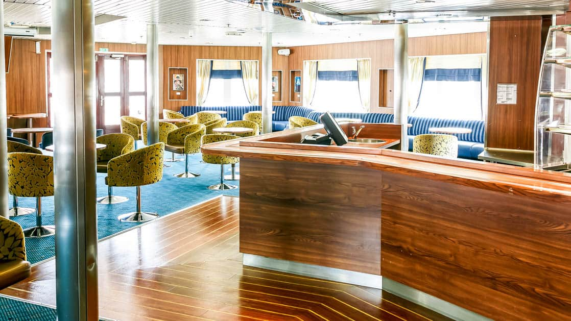 open room aboard Ocean Endeavour with a bar, tables and chairs