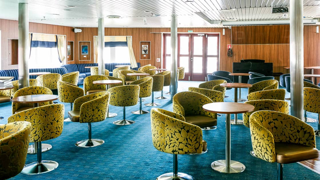 a lounge room with blue carpet and green chairs aboard Ocean Endeavour small ship